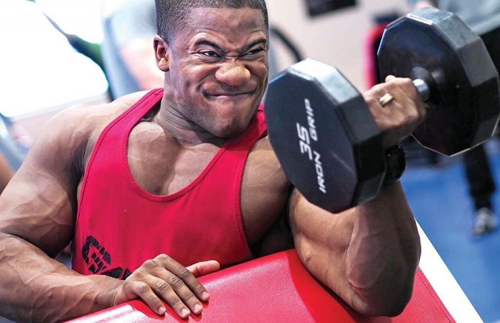 Atleta com um haltere exemplificando a contração muscular.